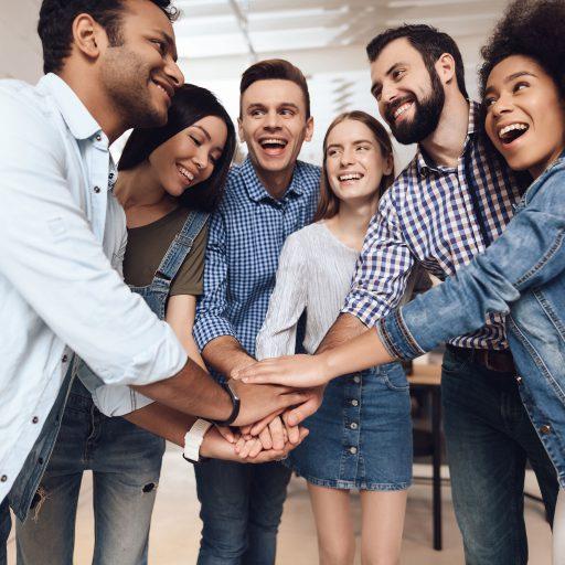 Un groupe de personne démontre de la collaboration en se joignant les mains
